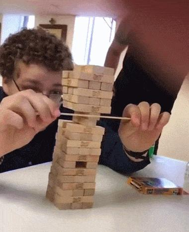 Guy skillfully removes block from tower with chopstick