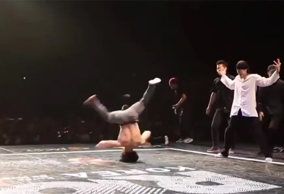 ⁣Breakdancer receives t-shirt from audience and puts it on.